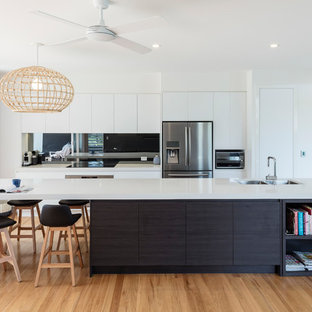 Photo of a large contemporary galley kitchen in Sunshine Coast with an undermount sink, flat-panel cabinets, white cabinets, metallic splashback, mirror splashback, stainless steel appliances, medium hardwood floors, with island, beige floor and white benchtop.