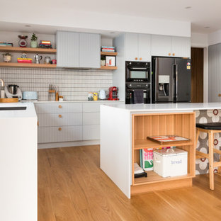 Photo of a midcentury l-shaped kitchen in Canberra - Queanbeyan with an undermount sink, flat-panel cabinets, grey cabinets, white splashback, mosaic tile splashback, medium hardwood floors, with island, brown floor and white benchtop.