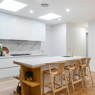 Inspiration for a contemporary l-shaped kitchen in Canberra - Queanbeyan with an undermount sink, quartz benchtops, white splashback, stone slab splashback, light hardwood floors, with island, flat-panel cabinets, white cabinets, panelled appliances, beige floor and white benchtop.
