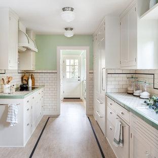 サクラメントのトラディショナルスタイルのおしゃれなII型キッチン (白いキャビネット、タイルカウンター、白いキッチンパネル、サブウェイタイルのキッチンパネル、パネルと同色の調理設備、シェーカースタイル扉のキャビネット) の写真