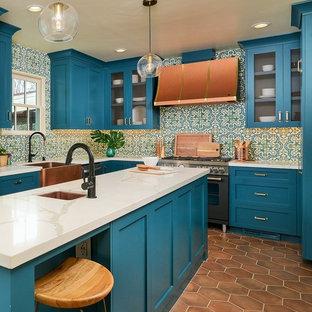 サクラメントの地中海スタイルのおしゃれなアイランドキッチン (シェーカースタイル扉のキャビネット、ターコイズのキャビネット、人工大理石カウンター、テラコッタタイルの床、白いキッチンカウンター) の写真