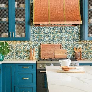 Esempio di una cucina mediterranea con ante in stile shaker, ante turchesi, top in superficie solida, pavimento in terracotta, isola e top bianco