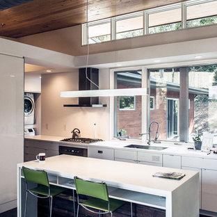 Modelo de cocina de galera, rústica, abierta, con armarios con paneles lisos, puertas de armario blancas, encimera de cuarcita, electrodomésticos de acero inoxidable, suelo de terrazo, una isla, suelo gris y encimeras blancas