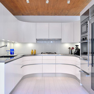 Inspiration for a small contemporary u-shaped separate kitchen in DC Metro with an integrated sink, flat-panel cabinets, white cabinets, stainless steel benchtops, glass sheet splashback, stainless steel appliances, bamboo floors and white splashback.