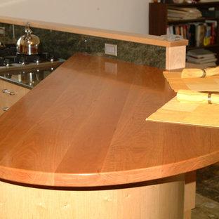 サンフランシスコの小さいコンテンポラリースタイルのおしゃれなキッチン (アンダーカウンターシンク、フラットパネル扉のキャビネット、淡色木目調キャビネット、木材カウンター、緑のキッチンパネル、石スラブのキッチンパネル、シルバーの調理設備、セラミックタイルの床、緑のキッチンカウンター) の写真