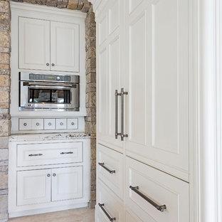 Offene, Geräumige Mediterrane Küche mit Kassettenfronten, weißen Schränken, Granit-Arbeitsplatte, bunter Rückwand, Rückwand aus Steinfliesen, Elektrogeräten mit Frontblende, Travertin und zwei Kücheninseln in Miami