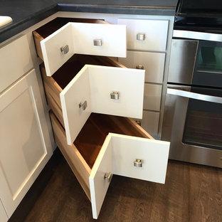 Diseño de cocina comedor en U, de estilo americano, de tamaño medio, con fregadero encastrado, armarios estilo shaker, puertas de armario blancas, encimera de laminado, electrodomésticos de acero inoxidable, suelo vinílico y una isla