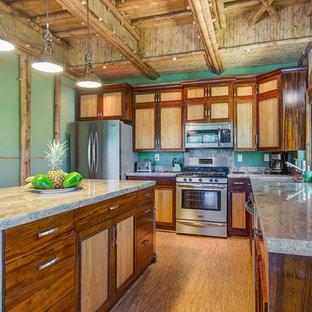 Imagen de cocina en L, tropical, abierta, con electrodomésticos de acero inoxidable, suelo de bambú y una isla