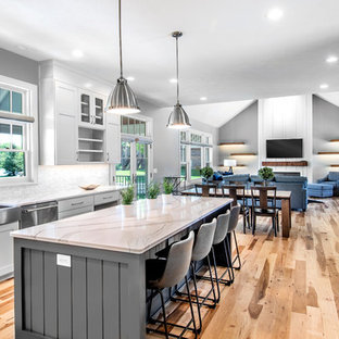 Mid-sized modern open concept kitchen inspiration - Mid-sized minimalist l-shaped medium tone wood floor and brown floor open concept kitchen photo in Omaha with a farmhouse sink, shaker cabinets, white cabinets, white backsplash, stone tile backsplash, stainless steel appliances, an island, white countertops and quartzite countertops