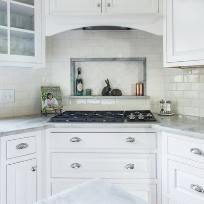 Example of a mid-sized classic u-shaped medium tone wood floor and beige floor kitchen design in Philadelphia with an undermount sink, beaded inset cabinets, white cabinets, quartzite countertops, white backsplash, ceramic backsplash, stainless steel appliances, an island and green countertops