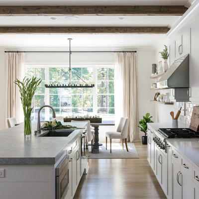 Example of a large transitional l-shaped light wood floor and brown floor eat-in kitchen design in Atlanta with an island, an undermount sink, shaker cabinets, white cabinets, limestone countertops, gray backsplash, porcelain backsplash and stainless steel appliances