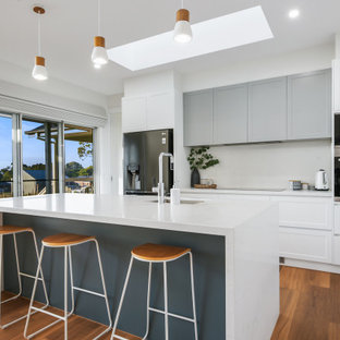 Photo of a mid-sized contemporary galley open plan kitchen in Other with an undermount sink, shaker cabinets, white cabinets, quartz benchtops, white splashback, black appliances, vinyl floors, with island, brown floor, white benchtop and stone slab splashback.