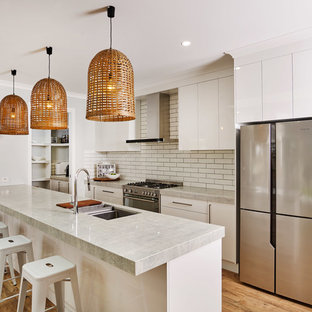 Photo of a mid-sized contemporary galley kitchen in Other with an undermount sink, flat-panel cabinets, white cabinets, quartz benchtops, white splashback, subway tile splashback, stainless steel appliances, laminate floors, with island, brown floor and grey benchtop.