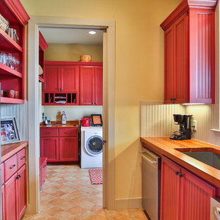 This is an example of a mid-sized country galley kitchen in Austin with an undermount sink, louvered cabinets, red cabinets, wood benchtops, yellow splashback, timber splashback, stainless steel appliances and ceramic floors.