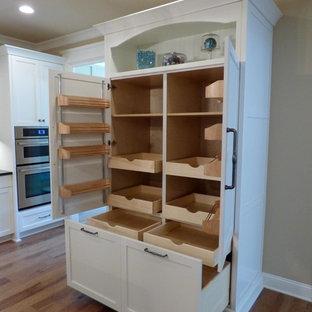 Exemple d'une grand cuisine craftsman avec un placard à porte shaker, des portes de placard blanches, un électroménager en acier inoxydable et un sol en bois brun.