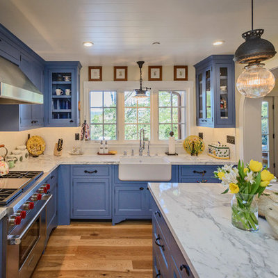 Example of a mid-sized country l-shaped medium tone wood floor and brown floor open concept kitchen design in San Francisco with a farmhouse sink, blue cabinets, marble countertops, white backsplash, subway tile backsplash, stainless steel appliances, an island and shaker cabinets