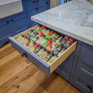 Inredning av ett lantligt mellanstort kök, med en rustik diskho, blå skåp, marmorbänkskiva, mellanmörkt trägolv, skåp i shakerstil, vitt stänkskydd, stänkskydd i tunnelbanekakel, rostfria vitvaror, en köksö och brunt golv