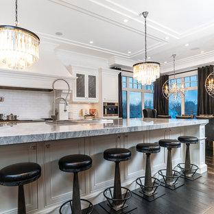 Неиссякаемый источник вдохновения для домашнего уюта: большая п-образная кухня с обеденным столом, фасадами с утопленной филенкой, белыми фасадами, столешницей из оникса, белым фартуком, фартуком из удлиненной плитки, техникой из нержавеющей стали, темным паркетным полом и островом