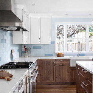Design ideas for a mid-sized beach style l-shaped open plan kitchen with a farmhouse sink, recessed-panel cabinets, distressed cabinets, quartz benchtops, blue splashback, glass tile splashback, stainless steel appliances, medium hardwood floors, with island, yellow floor and white benchtop.