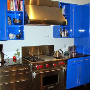 Offene, Zweizeilige, Mittelgroße Stilmix Küche mit flächenbündigen Schrankfronten, blauen Schränken, Granit-Arbeitsplatte, Küchenrückwand in Blau, Küchengeräten aus Edelstahl und dunklem Holzboden in New York