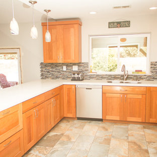 Mid-sized southwestern eat-in kitchen inspiration - Example of a mid-sized southwest u-shaped porcelain tile eat-in kitchen design in Los Angeles with an undermount sink, shaker cabinets, light wood cabinets, quartzite countertops, multicolored backsplash, mosaic tile backsplash, stainless steel appliances and a peninsula