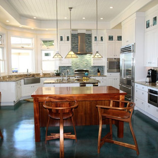 Inspiration for a large beach style kitchen in San Diego with a farmhouse sink, raised-panel cabinets, white cabinets, granite benchtops, blue splashback, glass tile splashback, stainless steel appliances, concrete floors, multiple islands, turquoise floor and multi-coloured benchtop.