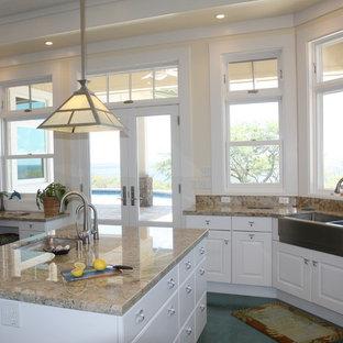 Foto på ett stort maritimt flerfärgad kök, med en rustik diskho, luckor med upphöjd panel, vita skåp, granitbänkskiva, blått stänkskydd, stänkskydd i glaskakel, rostfria vitvaror, betonggolv, flera köksöar och turkost golv