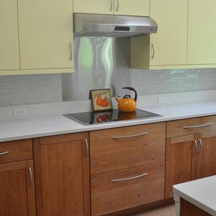 ボストンのモダンスタイルのおしゃれなキッチン (アンダーカウンターシンク、フラットパネル扉のキャビネット、黄色いキャビネット、クオーツストーンカウンター、白いキッチンパネル、ガラスタイルのキッチンパネル、シルバーの調理設備、コルクフローリング) の写真