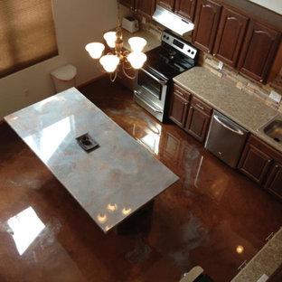 他の地域の大きいインダストリアルスタイルのおしゃれなキッチン (ドロップインシンク、レイズドパネル扉のキャビネット、中間色木目調キャビネット、御影石カウンター、マルチカラーのキッチンパネル、石タイルのキッチンパネル、シルバーの調理設備の、コンクリートの床、茶色い床) の写真