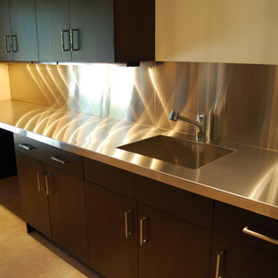 Photo of a mid-sized transitional galley separate kitchen in Chicago with an undermount sink, shaker cabinets, dark wood cabinets, stainless steel benchtops, metallic splashback, metal splashback, stainless steel appliances, porcelain floors, with island and beige floor.