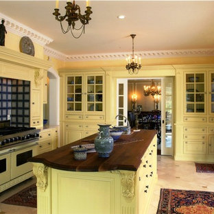 Example of a classic enclosed kitchen design in Bridgeport with yellow cabinets, wood countertops, colored appliances, raised-panel cabinets and multicolored backsplash