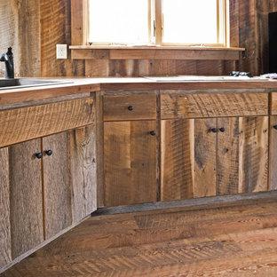 他の地域の中サイズのラスティックスタイルのおしゃれなキッチン (ドロップインシンク、フラットパネル扉のキャビネット、ヴィンテージ仕上げキャビネット、木材カウンター、茶色いキッチンパネル、木材のキッチンパネル、黒い調理設備、無垢フローリング) の写真