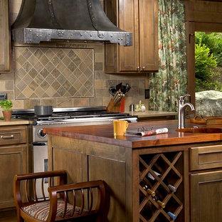 Rustikale Küche mit Schrankfronten mit vertiefter Füllung, hellbraunen Holzschränken, Arbeitsplatte aus Holz, bunter Rückwand, Küchengeräten aus Edelstahl und Rückwand aus Schiefer in Sonstige