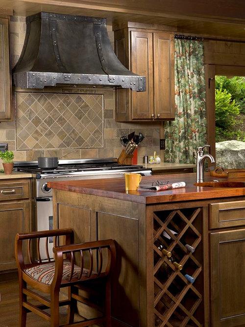 Rustikale küche mit schrankfronten mit vertiefter füllung hellbraunen holzschränken arbeitsplatte aus holz bunter