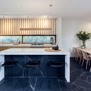 This is an example of a midcentury galley eat-in kitchen in Melbourne with an undermount sink, flat-panel cabinets, light wood cabinets, window splashback, stainless steel appliances, with island, black floor and white benchtop.
