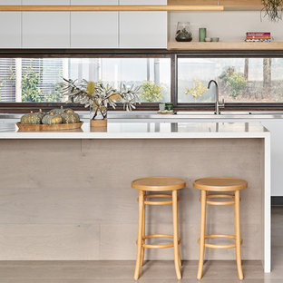 Photo of a large contemporary galley kitchen in Melbourne with flat-panel cabinets, white cabinets, window splashback, medium hardwood floors, with island, brown floor and white benchtop.