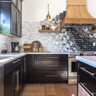 ミネアポリスの中サイズのエクレクティックスタイルのおしゃれなキッチン (アンダーカウンターシンク、シェーカースタイル扉のキャビネット、黒いキャビネット、珪岩カウンター、マルチカラーのキッチンパネル、セラミックタイルのキッチンパネル、シルバーの調理設備の、淡色無垢フローリング、マルチカラーの床、白いキッチンカウンター) の写真