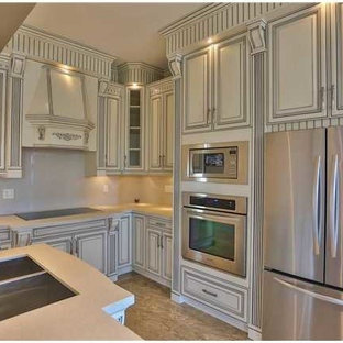 This is an example of a large asian u-shaped eat-in kitchen in Vancouver with an undermount sink, beige cabinets, quartzite benchtops, white splashback, glass sheet splashback, stainless steel appliances, marble floors and with island.