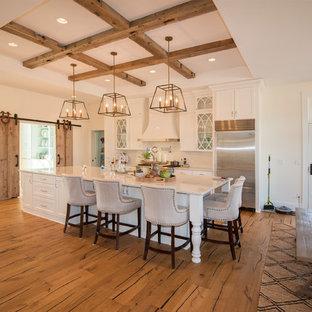 ミルウォーキーの大きいエクレクティックスタイルのおしゃれなキッチン (エプロンフロントシンク、シェーカースタイル扉のキャビネット、白いキャビネット、大理石カウンター、白いキッチンパネル、セラミックタイルのキッチンパネル、シルバーの調理設備、無垢フローリング、茶色い床、白いキッチンカウンター) の写真