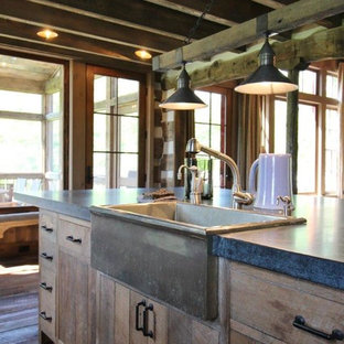 This is an example of a mid-sized country l-shaped open plan kitchen in Other with a farmhouse sink, flat-panel cabinets, distressed cabinets, zinc benchtops, medium hardwood floors and with island.