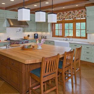 他の地域の広いラスティックスタイルのおしゃれなキッチン (エプロンフロントシンク、シェーカースタイル扉のキャビネット、緑のキャビネット、御影石カウンター、サブウェイタイルのキッチンパネル、シルバーの調理設備、コルクフローリング、白いキッチンパネル) の写真