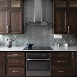 Idéer för att renovera ett mellanstort amerikanskt svart linjärt svart kök med öppen planlösning, med en undermonterad diskho, skåp i shakerstil, skåp i mörkt trä, granitbänkskiva, grått stänkskydd, stänkskydd i keramik, rostfria vitvaror, laminatgolv och grått golv