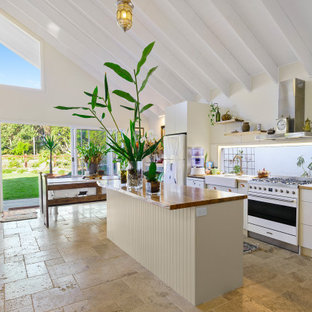 This is an example of a beach style galley kitchen in Gold Coast - Tweed with a farmhouse sink, flat-panel cabinets, white cabinets, wood benchtops, white appliances, with island, beige floor and brown benchtop.