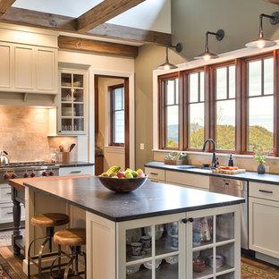 Immagine di una cucina classica con lavello sottopiano, ante di vetro, ante bianche, paraspruzzi beige, elettrodomestici in acciaio inossidabile e isola
