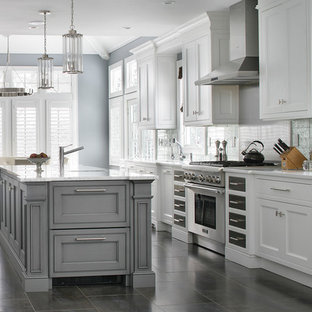 Photo of a traditional galley kitchen/diner in New York with beaded cabinets, white cabinets, stainless steel appliances, an island, grey splashback and white worktops.