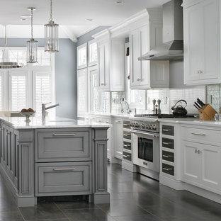 Klassisk inredning av ett kök, med luckor med profilerade fronter, vita skåp, stänkskydd med metallisk yta, rostfria vitvaror och en köksö