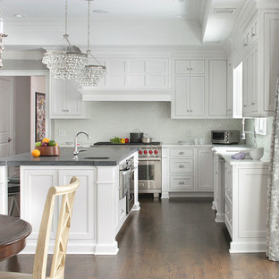 Inspiration for a traditional u-shaped kitchen/diner in New York with shaker cabinets, white cabinets, white splashback, stainless steel appliances, dark hardwood flooring and an island.