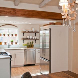 アルバカーキの中くらいのサンタフェスタイルのおしゃれなキッチン (アンダーカウンターシンク、シェーカースタイル扉のキャビネット、白いキャビネット、青いキッチンパネル、ガラスタイルのキッチンパネル、シルバーの調理設備、淡色無垢フローリング、アイランドなし、ベージュの床) の写真