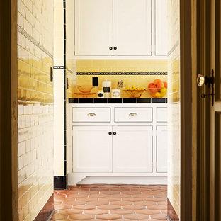 ロサンゼルスの中サイズの地中海スタイルのおしゃれな独立型キッチン (落し込みパネル扉のキャビネット、白いキャビネット、タイルカウンター、黄色いキッチンパネル、サブウェイタイルのキッチンパネル、カラー調理設備、テラコッタタイルの床、赤い床、マルチカラーのキッチンカウンター、エプロンフロントシンク、アイランドなし) の写真