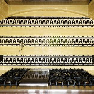 ロサンゼルスの中サイズの地中海スタイルのおしゃれな独立型キッチン (エプロンフロントシンク、落し込みパネル扉のキャビネット、白いキャビネット、タイルカウンター、黄色いキッチンパネル、サブウェイタイルのキッチンパネル、カラー調理設備、テラコッタタイルの床、アイランドなし、赤い床、マルチカラーのキッチンカウンター) の写真
